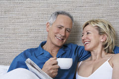 Couple With Coffee Cup Reading Newspaper In Bed Royalty Free Stock Photo