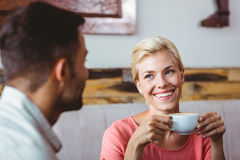Couple with coffee cup sitting on sofa Stock Images