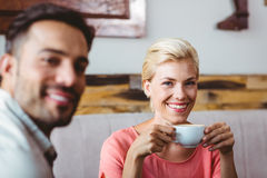 Couple with coffee cup sitting on sofa Royalty Free Stock Photo