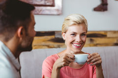 Couple with coffee cup sitting on sofa Stock Photo