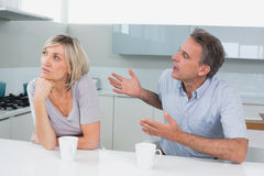 Couple with coffee cups having a fight in kitchen Stock Photo