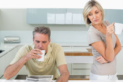 Couple with coffee cups reading newspaper in kitchen Royalty Free Stock Image
