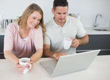 Couple with coffee cups using laptop at table Royalty Free Stock Photo