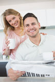 Couple with coffee mugs and newspaper in kitchen Stock Photos