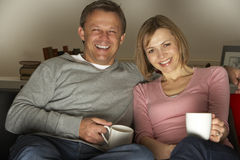 Couple With Coffee Mugs Watching Television Stock Images