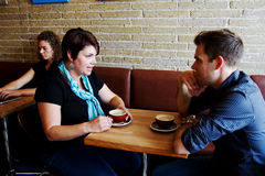 Couple in coffee shop. Couple expressing concerns in coffee shop Royalty Free Stock Photography