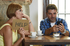 Couple at coffee shop mobile phone addict man ignoring frustrated woman asking for help Stock Images