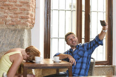 Couple at coffee shop with mobile phone addict man taking selfie photo ignoring bored sad and frustrated woman Royalty Free Stock Photo