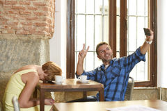 Couple at coffee shop with mobile phone addict man taking selfie photo ignoring bored sad and frustrated woman. Young American couple at coffee shop with mobile stock images