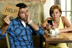 Couple at coffee shop  mobile phone addict woman ignoring frustrated man asking for help Stock Images