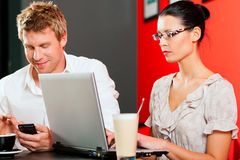 Couple in coffeeshop with laptop and mobile Stock Images