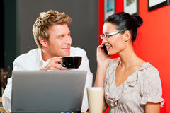 Couple in coffeeshop with laptop and mobile Royalty Free Stock Image
