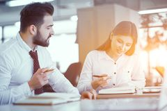 A couple of colleagues at desk in sunny office. Business Colleagues Correcting Business Plan While Being In Sunny Boardroom. Holding Pens. Business Concept stock image