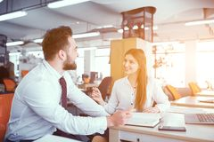 A couple of colleagues at desk in sunny office. Business Conversation Of Skilled Male And Female Colleagues In Sunny Modern Office. Solving Business Issues royalty free stock photo