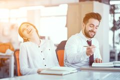 A couple of colleagues at desk in sunny office. Girl In Office Clothes Laughs With Her Head Thrown Back. Her Male Colleague Making Notes. Business In Office stock photos