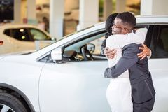 Couple collecting new car from salesman on lot. Couple collecting a new car from salesman on lot royalty free stock image