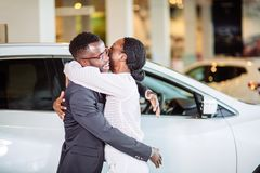 Couple collecting new car from salesman on lot. Beautiful young african couple is smiling, looking at camera and hugging while buying car in motor show royalty free stock image