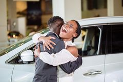 Couple collecting new car from salesman on lot. Beautiful young african couple is smiling, looking at camera and hugging while buying car in motor show royalty free stock photography
