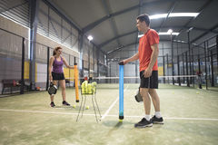 Couple collects balls with tube after paddle class to continue t. Raining Stock Photography