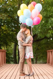 Couple with colorful balloons kissing in the park Stock Photography