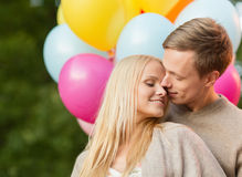 Couple with colorful balloons kissing in the park Royalty Free Stock Image