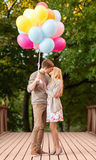 Couple with colorful balloons kissing in the park Stock Photos