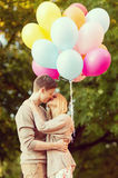 Couple with colorful balloons kissing in the park Stock Image