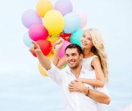 Couple with colorful balloons at sea side Stock Images