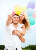 Couple with colorful balloons at sea side Stock Photography