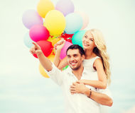 Couple with colorful balloons at sea side Stock Photos