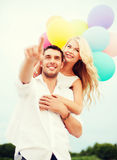 Couple with colorful balloons at sea side Royalty Free Stock Photos