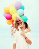 Couple with colorful balloons at seaside Royalty Free Stock Photo