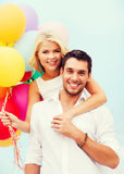 Couple with colorful balloons at seaside Stock Photo