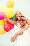 Couple with colorful balloons at seaside Stock Images