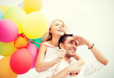 Couple with colorful balloons at seaside Stock Photos