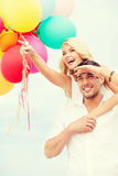 Couple with colorful balloons at seaside Royalty Free Stock Photos