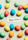 Couple of colorful eggs surrounding white paper with easter wishes. Christian holiday Royalty Free Stock Images