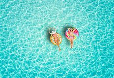 Couple on colorful floats over turquoise colored sea of the Maldives