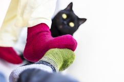 Couple in Colorful Woolen Knitted Socks Touching Each Other Feet. Black Cat Watching.  People Relaxing At Home in Cold Season. Christmas, New Year, Love royalty free stock photo
