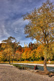 Couple in colourful autumn. Young couple sitting at a river looking at wonderful autumn landscape (HDR Stock Photos