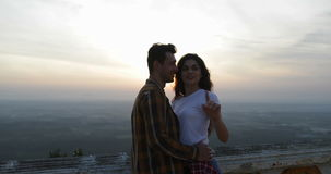 Couple coming to mountain top embracing, girl point finger, tourists man and woman engoying lanscape. Slow Motion 60 stock footage
