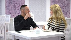 A guy and a girl communicate in a cafe with a Cup of tea. Couple communicate in a cafe with a Cup of tea stock video
