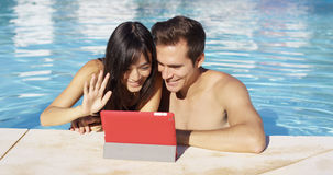 Couple communicates with friends on digital device Stock Photography