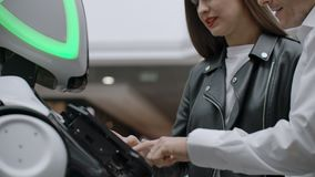 The couple communicates with robot assistant with information screen in duty to give information. Contact with the robot stock video