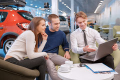 Couple communicating with the salesman in showroom. Your new car will be exactly the same. Sales consultant showing to the smiling couple information about their Royalty Free Stock Image