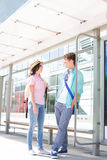 Couple communicating while waiting at bus stop Royalty Free Stock Photos