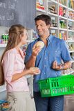 Couple Comparing Cheese At Grocery Store Royalty Free Stock Photos