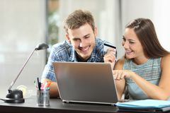 Couple comparing products buying on line with a laptop. Happy couple comparing online products buying on line with a laptop and credit card royalty free stock photography