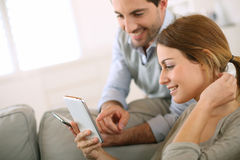 Couple comparing smartphones at home Stock Images