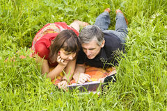 Couple with computer on grass Royalty Free Stock Images